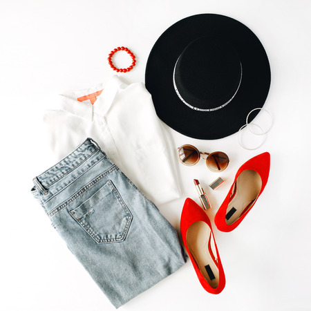high view: flat lay feminini clothes and accessories collage with blouse, jeans, sunglasses, bracelet, lipstick, red high heel shoes, earrings and hat on white background.
