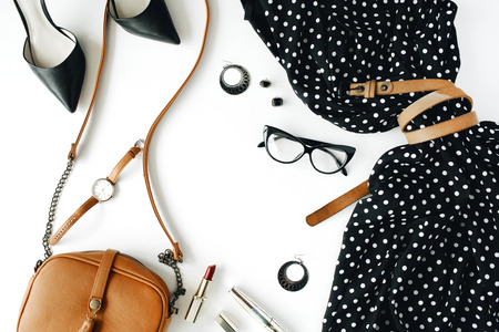 flat lay feminini clothes and accessories collage with black dress, glasses, high heel shoes, purse, watch, mascara, lipstick, earrings on white background. Reklamní fotografie