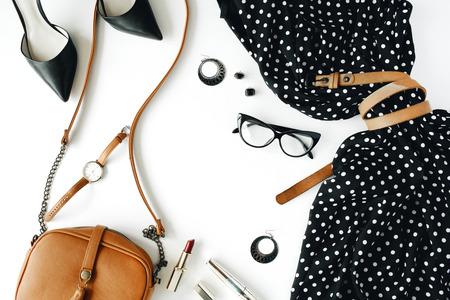 plat leggen feminini kleding en accessoires collage met zwarte jurk, bril, hoge hak schoenen, portemonnee, horloge, mascara, lippenstift, oorbellen op witte achtergrond.