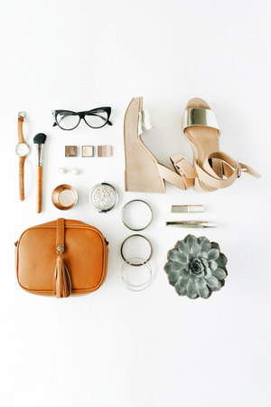 plat feminini accessoires collage met portemonnee, horloge, bril, armband, lippenstift, sandalen, mascara, borstels op een witte achtergrond.