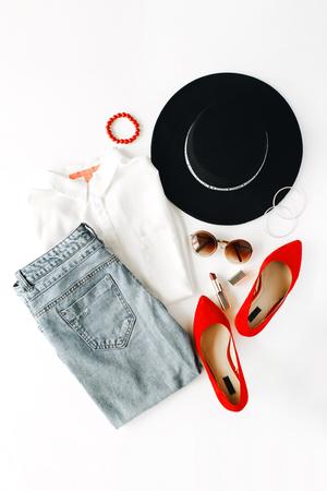 フラット レイアウト feminini ブラウス、ジーンズ、サングラス、ブレスレット、口紅、赤いハイヒールの靴、イヤリング、白い背景の上の帽子と服や 写真素材