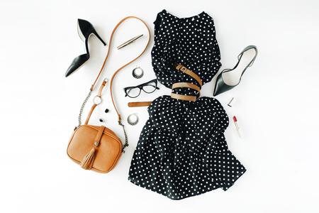 フラット レイアウト feminini の服やアクセサリーは、黒のドレス、メガネ、ハイヒールの靴、財布、時計、マスカラー、口紅、白い背景の上のイヤリ 写真素材