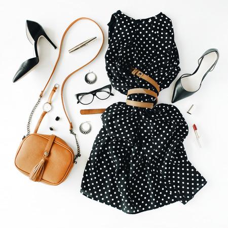 plat feminini kleding en accessoires collage met zwarte kleding, brillen, schoenen met hoge hakken, portemonnee, horloge, mascara, lippenstift, oorbellen op een witte achtergrond. Stockfoto