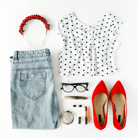 flat lay feminine clothes and accessories collage with shirt, jeans, glasses, mascara, lipstick, red high heel shoes, earrings and hoop on white background.