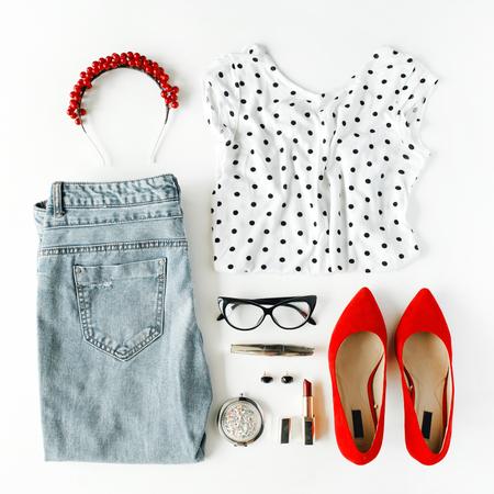 plat vrouwelijke kleding en accessoires collage met shirt, jeans, glazen, mascara, lippenstift, rode schoenen met hoge hakken, oorbellen en hoepel op een witte achtergrond. Stockfoto