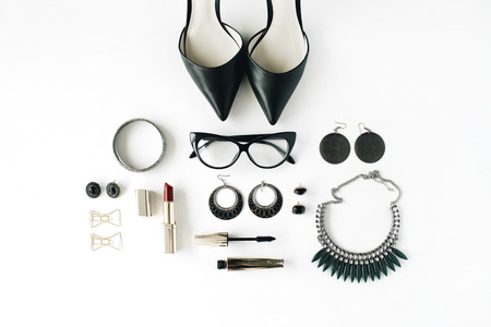 flat lay feminine accessories collage with glasses, high heel shoes, mascara, lipstick, bracelet, earrings, necklace and bow tie clips on white background.