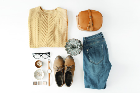 flat lay feminine clothes and accessories collage with brown cardigan, jeans, glasses, watch, earrings, purse, boots and succulent on white background. Imagens