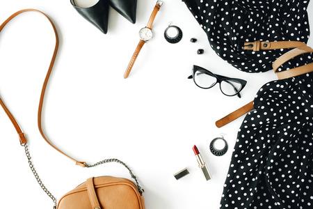 plat vrouwelijke kleding en accessoires collage met zwarte kleding, brillen, schoenen met hoge hakken, portemonnee, horloge, mascara, lippenstift, oorbellen op een witte achtergrond.
