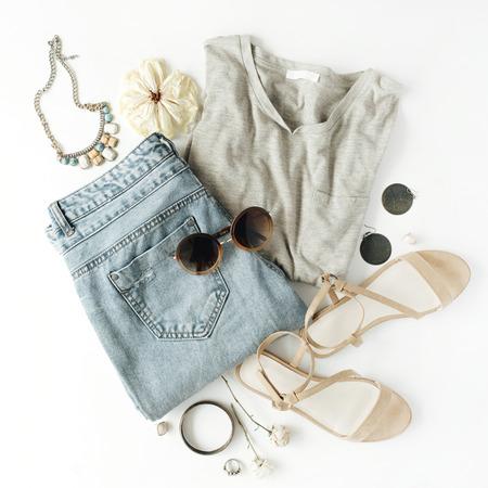 Vêtements et collants d'accessoires féminins et plats, chemises, jeans, lunettes de soleil, bracelet, sandales, boucles d'oreilles sur fond blanc.