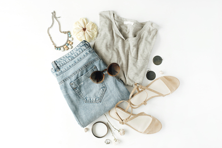 flat lay feminine clothes and accessories collage with shirt, jeans shorts, sunglasses, bracelet, sandals, earrings on white background.