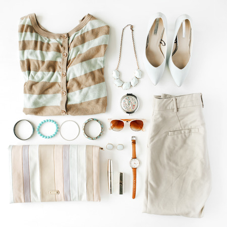 flat lay feminine clothes and accessories collage with cardigan, trousers, sunglasses, watch, bracelet, lipstick, mint high heel shoes, earrings and purse on white background. Zdjęcie Seryjne