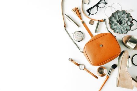 Ploché ležel ženský doplňky koláž s kabelkou, hodinky, brýle, náramek, rtěnka, sandály, řasenka, štětce na bílém pozadí.