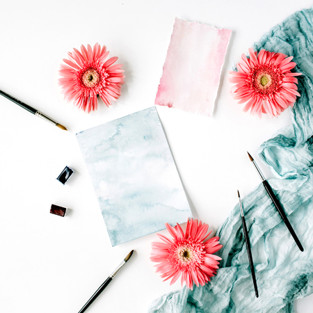 Workspace. Pink gerbera buds and watercolor paper with paintbrush and blue textile on white background. Flat lay, top view Zdjęcie Seryjne