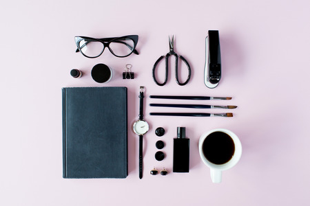 flat brushes: Flat lay, top view black style office table desk. feminine working supplies: glasses, diary, watches, perfume, brushes, scissors, coffee on pink background.