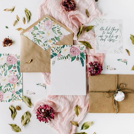 작업 영역. 결혼식 초대 카드, 공예 봉투, 분홍색 및 빨강 장미 및 녹색 흰색 배경에 나뭇잎. 오버 헤드보기입니다. 평평한 평면, 평면도