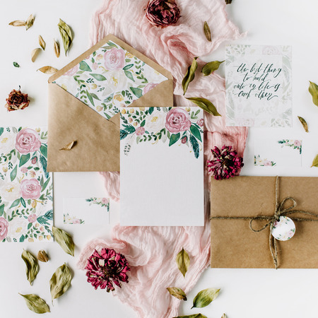 Workspace. Wedding invitation cards, craft envelopes, pink and red roses and green leaves on white background. Overhead view. Flat lay, top view Standard-Bild