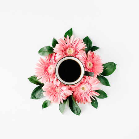 black coffee mug and pink gerbera flowers bouquet on white background. flat lay, top view