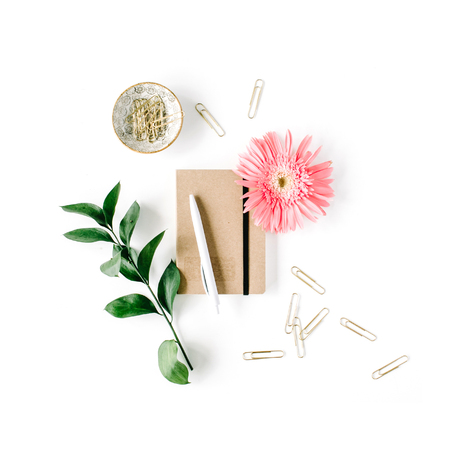 pink gerbera daisy, green branch, golden clips, craft diary and pen on white background. flat lay, top view