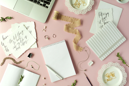Flat lay, top view office table desk. feminine desk workspace with laptop, diary, spool with ribbon, calligraphy quotes and golden clips on pink background.