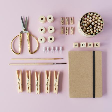 평면 누워, 상위 뷰 갈색 에코 스타일 사무실 책상 책상입니다. 여성 작업 공급 : 공예 일기, 연필 상자, 브러쉬, 황금가 위, 스풀, 분홍색 배경에 핀. 스톡 콘텐츠