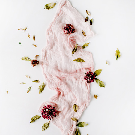 decorated composition with dry red roses, petals and pink textile on white background. flat lay, top view Zdjęcie Seryjne