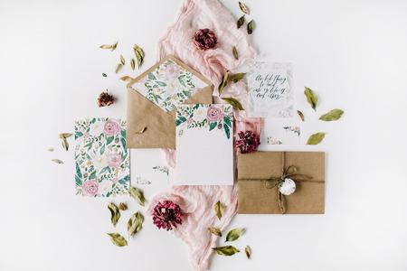 ワークスペースです。結婚式の招待カード、クラフト封筒、ピンクと赤のバラとグリーンの白い背景の葉します。オーバーヘッドのビュー。フラッ