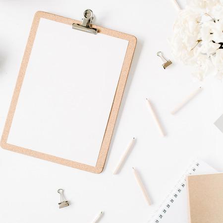평면 누워, 상위 뷰 사무실 책상 책상. 여성 책상 작업 공간 조롱 클립 보드, 꼬기, 연필, 꽃 꽃다발, 공예 일기 및 흰색 배경에 클립. 스톡 콘텐츠