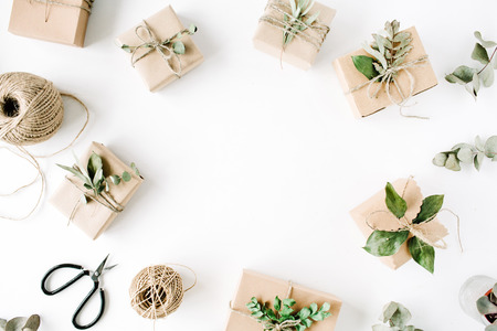 creative arrangement frame of craft boxes and green branches on white background. flat lay, top view