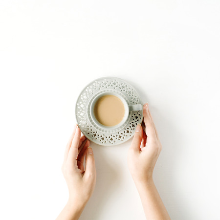 girl's hands holding coffee cup. flat lay, top view Zdjęcie Seryjne