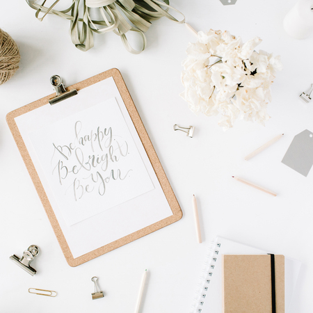 Flat lay, top view office table desk. feminine desk workspace with clipboard and inspirational quote, twine, pencils, floral bouquet, craft diary and clips on white background. 版權商用圖片