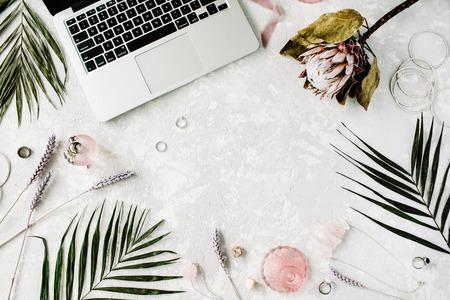 plat vrouwelijke kantoor aan huis werkruimte met laptop, Proteus bloem, ketting, palmtakken en accessoires. bovenaanzicht Stockfoto