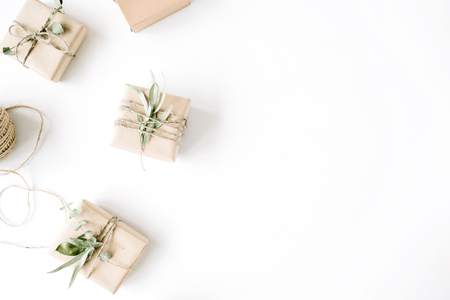 white party: creative arrangement pattern of craft boxes and green branches on white background. flat lay, top view Stock Photo