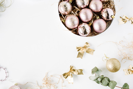 tinsel: frame made of christmas decoration with christmas glass balls, tinsel, bow, eucalyptus. christmas wallpaper. flat lay, top view