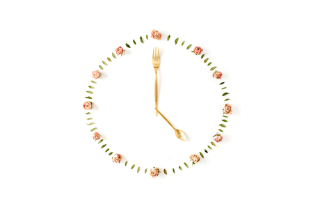 seconds: flat lay clock face made of rose buds, spoon and fork. top view