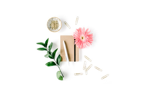 gerbera daisy: pink gerbera daisy, green branch, golden clips, craft diary and pen on white background. flat lay, top view