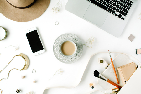 Flat lay trendy feminine home office workspace. Laptop, coffee cup, phone, purse, hat, female accessories. Top view