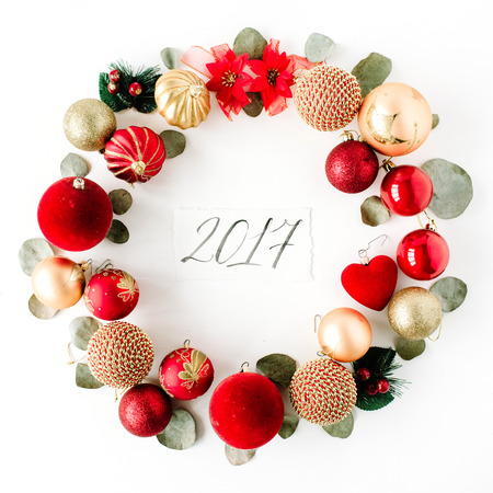christmas wreath frame made of colored bright christmas balls and calligraphy year 2017 on white background. flat lay, top view Фото со стока