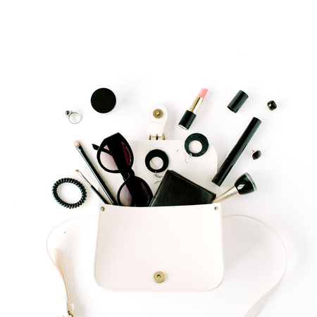 flat lay feminine arrangement with wallet, accessories, purse, cosmetics, sunglasses on white, flat lay, top view