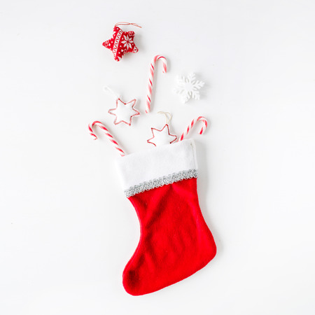 creative arrangement of bright red christmas toys in christmas sock on white background. flat lay, top view