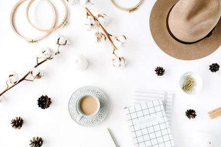 플랫 누워 유행 창조적 인 여성 액세서리 커피, 면화 지점 및 일기와 함께 정렬합니다. 모자, 코 튼 분기, 노트북, 커피 컵, 전나무 콘, 흰색 배경에 황금