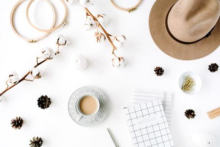 Flat lay trendy creative feminine accessories arrangement with coffee, cotton branch and diary. Hat, cotton branch, notebook, coffee cup, fir cone, golden clips on white background. Top view Stok Fotoğraf