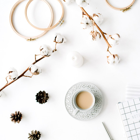 Flat était à la mode créative accessoires féminins arrangement avec le café, le coton et la branche journal. Chapeau, coton branche, ordinateur portable, café, pomme de pin, des clips d'or sur fond blanc. vue de dessus
