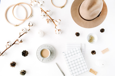 Flat lay trendy creative feminine accessories arrangement with coffee, cotton branch and diary. Hat, cotton branch, notebook, coffee cup, fir cone, golden clips on white background. Top view Zdjęcie Seryjne