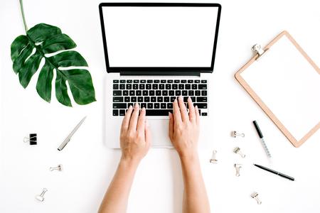 Espacio de trabajo con manos escribiendo en la computadora portátil con pantalla en blanco. Plano, vista desde arriba Foto de archivo - 69222873