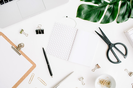 Kantoor aan huis werkruimte met laptop, klembord, palmblad, notebook en accessoires. Plat leggen, bovenaanzicht
