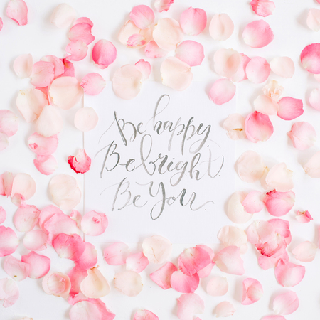 Be bright. Be happy. Be you. Inspirational quote made with calligraphy and floral pattern with pink rose petals. Flat lay, top view