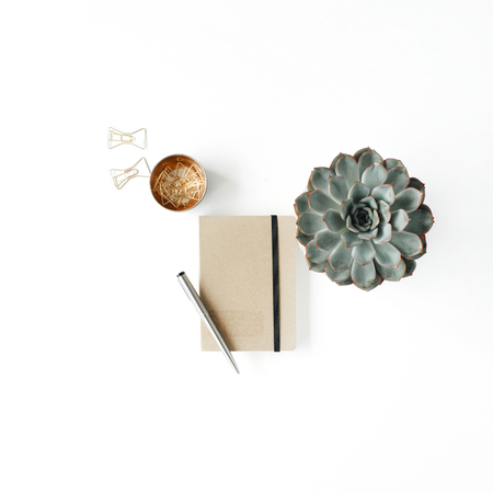 Feminine home office workspace with succulent, diary and golden clips on white background. Flat lay, top view
