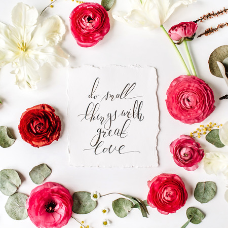 Quote Do small things with great love written in calligraphic style on paper with pink, red roses, ranunculus, white tulips and green leaves on white background. Flat lay, top view