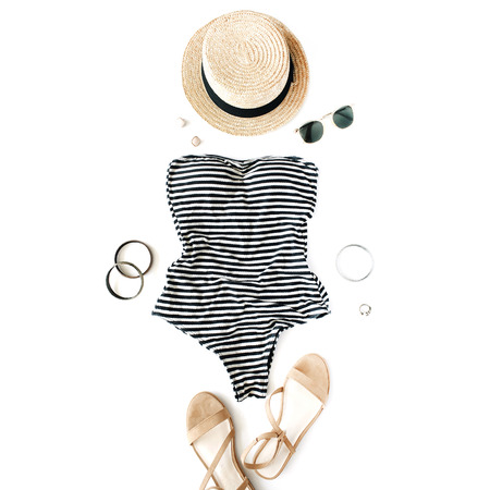 Feminine swimsuit beach accessories on white background. Flat lay, top view