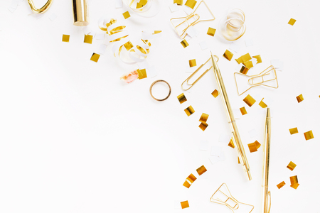 feminine background: Beauty blog background. Gold style feminine accessories. Golden tinsel, pen, rings on white background. Flat lay, top view.